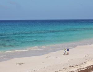 "Sylvia and Tom walk the beach on ""Great Guyna Cay"""